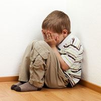 Boy Sitting in a Corner Covering His Face